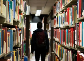 A boy walks through an aisle of books in a library.