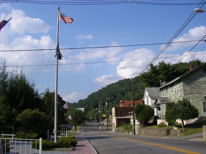 A small town main street with a green mountain in the background and an American flag