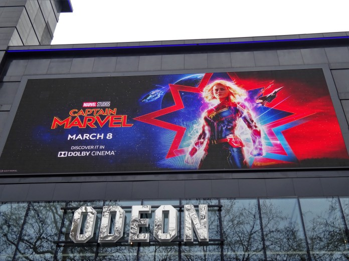 Photograph of a Captain Marvel poster above a movie theatre entrance; the poster shows Brie Larson as Captain Marvel standing with a star and flashing lights behind her