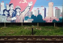 Graffiti image of three happy individuals under communist flag with Vietnam skyline behind
