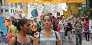 "Two young women in the foreground of a protest march, with signs behind them saying ""our future our choice"""