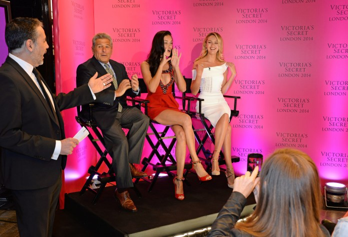 Photograph of two women in dresses and a man on a stage with a Victoria's Secret pink background