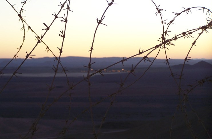 photograph of barbed wire fence with camp in the distance