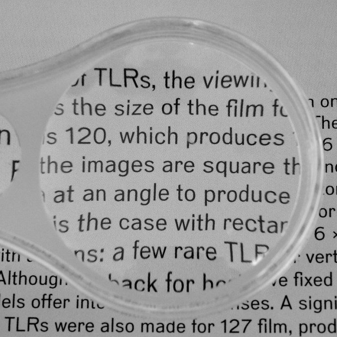 photograph of magnifying glass examining text