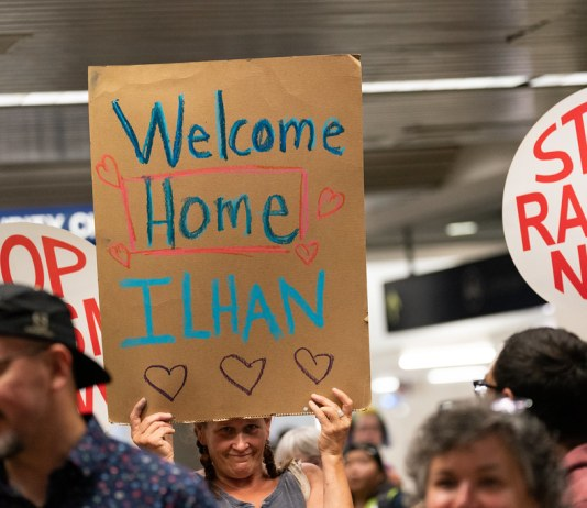 "photograph of ""Welcome Home Ilhan"" sign held by supporter with others gathered at MSP"
