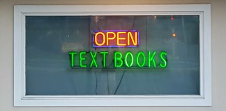"""photograph of neon """"Open"""" and """"Textbooks"""" signs in window"""