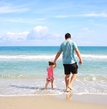 photograph of father walking with daughter in the water on the beach