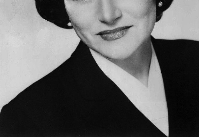 Cropped, black-and-white headshot of a white woman with dark hair, pearl earrings wearing a white blouse and dark blazer.