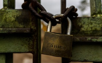cloeup photograph of lock on gate with iron chain