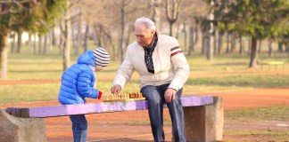 photograph of grandfather and grandson playing chess on a bench outdoors