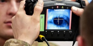 photograph of two army personnel using biometric scanner