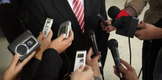 photograph of reporters' recording devices pushing for response from suited figure
