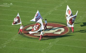 photograph of 49er flagbearers celebrating on field