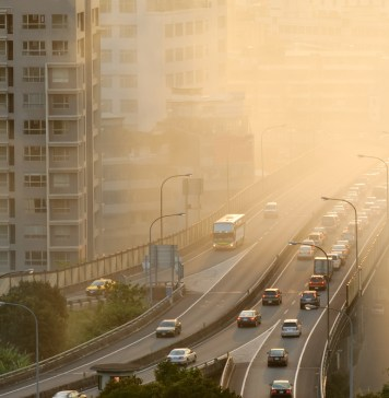 photograph of air pollution with cars on highway and yellow smoke in city