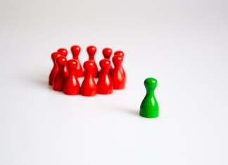 photograph of green board game piece isolated from huddled, red board game pieces