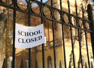 "photograph of gate to school with ""SCHOOL CLOSED"" sign"