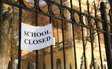 """photograph of gate to school with """"SCHOOL CLOSED"""" sign"""