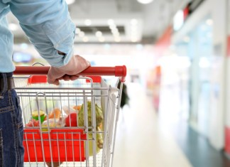 photograph of well-dressed youth shopping in grocery store with cart