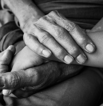 black and white photograph of old and young hands touching