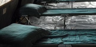 photograph of empty cots in a medical tent