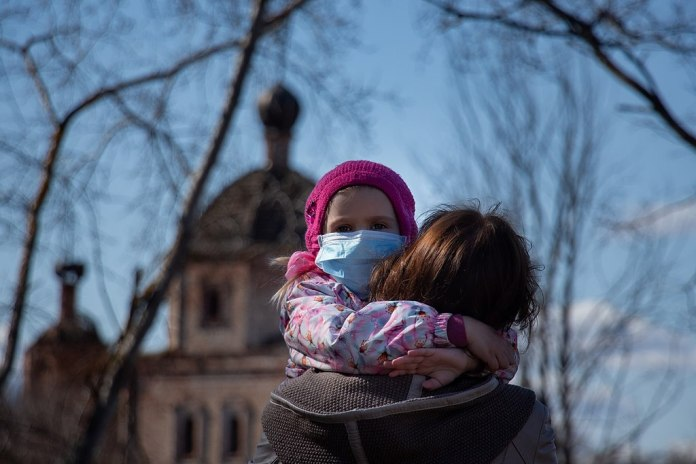 photograph of child with mask hugging her mother