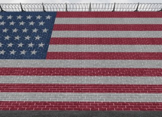 photograph of American flag painted on side of brick wall with barb wire strung on top