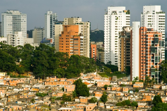 photograph of Sao Paulo favelabutting up against expensive buildings in background