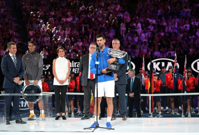 photograph of Djokovic on stage at mic with trophy in front of packed stadium