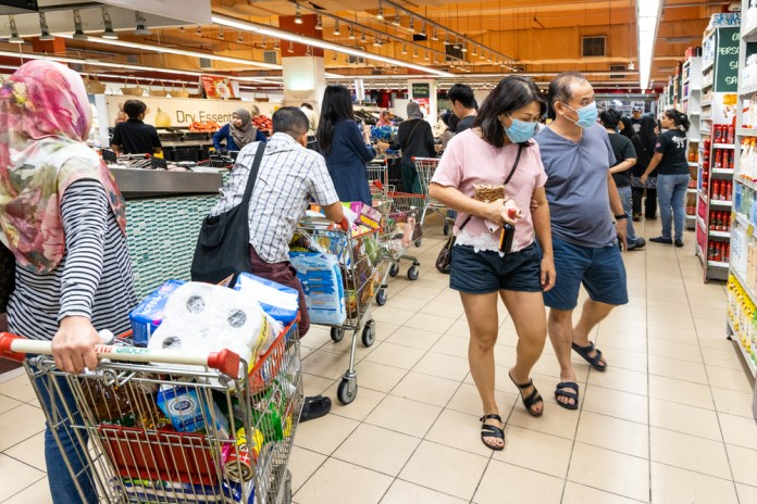 photograph of crowded grocery store with customers wearing masks