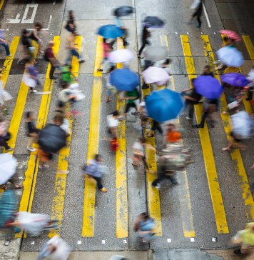 photograph of blurred pedestrians crossing intersection