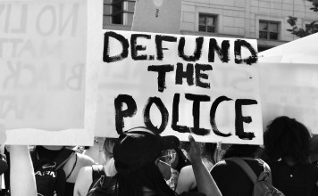 "black-and-white photgraph of protestors holding ""Defund the Police"" sign"