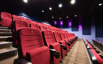 photograph of empty movie theater with lights up