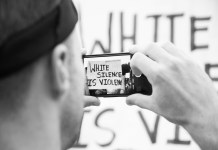 "black-and-white photograph of protestor taking photo of ""White Silence is Violence"" sign with phone"