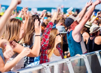photograph of teenagers at corwded concert on the beach