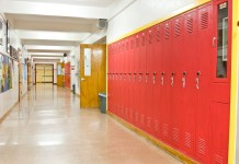 photograph of an empty highschool hallway with lockers on the right side