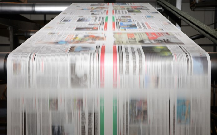 photograph of newspaper printing press in operation