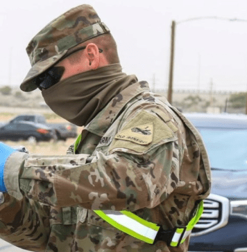 photograph of army reserve personnel wearing neck gaiter at covid testing site