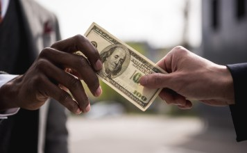 photograph of hands exchanging a one hundred dollar banknote