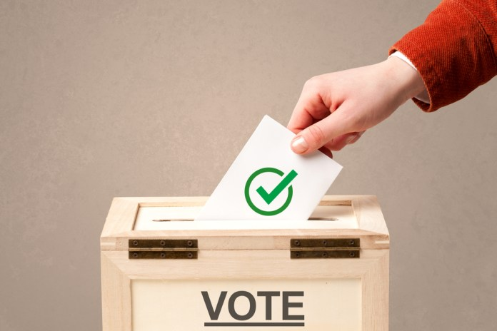 close up photograph of male hand putting vote into a ballot box