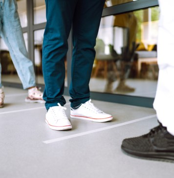 photograph of patients' feet standing in line waiting to get tested for COVID