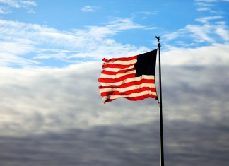 photograph of worn USA flag on pole with clouds behind