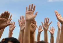 photograph of group of hands raised