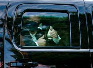 photograph of President Trump with face mask giving thimbs up from within SUV