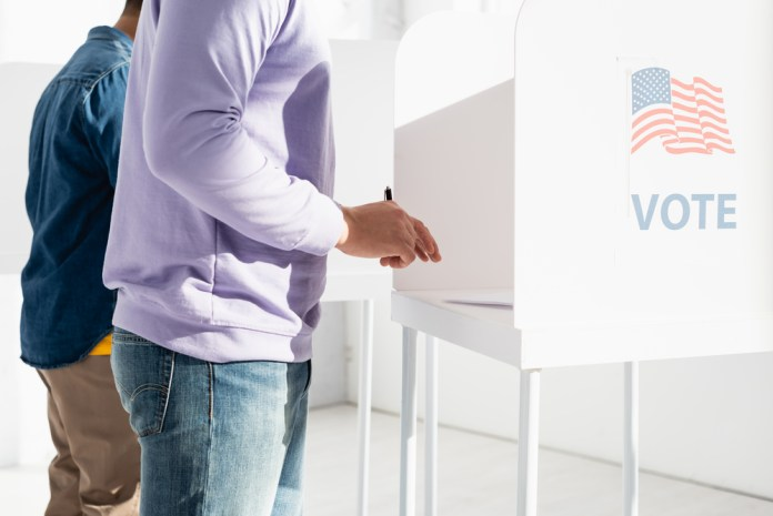 photograph of citizens filling out voting ballots with
