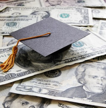 photograph of college graduation cap laying on top of pile of cash