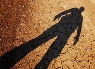photograph of human shadow stretching out over dry lakebed