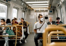 photograph of full subway car with half of the passengers unmasked