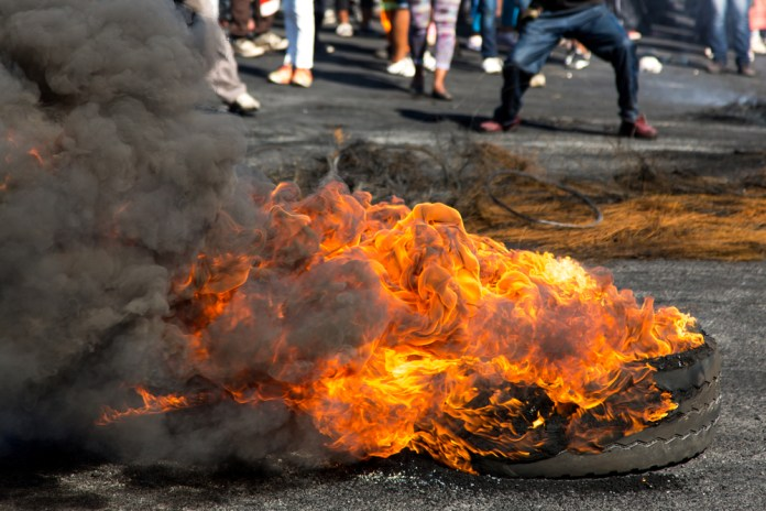 photograph of a burning tire with the feet of a crowd of protestors in the background
