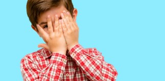 photograph of small child peeking through his hands covering his face