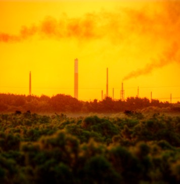 photograph of industrial chimney stacks polluting air over natural landscape